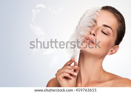 Beautiful young girl with large white feather near face. clean soft body products. Beauty Portrait. Woman Touching. Perfect Fresh Skin. Youth and Skin Care Concept. Isolated on blue background