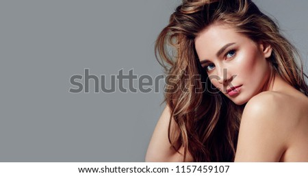 Beautiful young girl with long curly hair posing in studio in different poses against a gray background. #1157459107