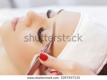 Beautiful young girl with long eyelashes tweezing her eyebrows in a beauty salon. Beauty Concept. Permanent Makeup. Microblading brow.  Beautician Doing eyebrow Tattooing. Close up view. #1097437133