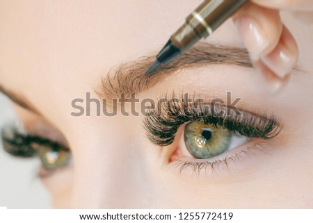 Beautiful young girl with long eyelashes tweezing her eyebrows in a beauty salon. Eyebrow Correction. Beauty Concept. Permanent Makeup. Microblading brow. Beautician Doing brows Tattooing. Treatment.