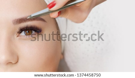 Beautiful young girl with long eyelashes tweezing her eyebrows in a beauty salon. Woman doing eyebrow permanent makeup correction . Microblading brow.