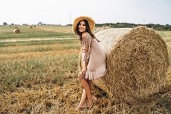 Beautiful young girl with long hair in sunnglasses and straw hat posing on a wheat field near hay bales. Happy brunette in summer dress.