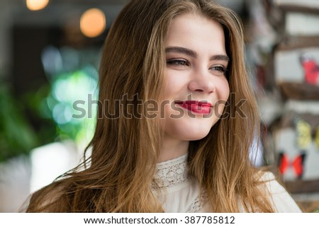 Beautiful young girl with makeup and hairstyle sitting in restaurant.