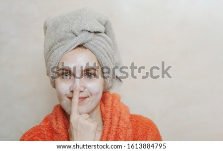 Beautiful young girl with natural ecological homemade mask on her face touching and smearing her nose in bathroom. Skin care, eco care, health care concept. Place for your text, copy space