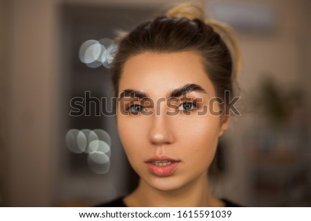 Beautiful young girl with natural make-up and beautifully laid eyebrows.