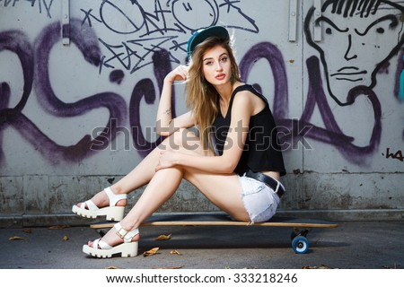 Stock Photo Beautiful young girl, with tattoo on her arm, wearing in cap, sandals, shirt and shorts, posing on her skateboard, near the wall with graffiti, in the park, full body