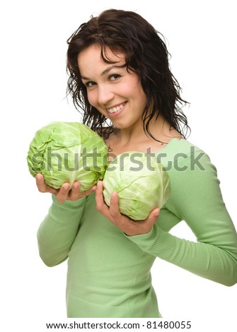Beautiful young girl with two green cabbages, isolated over white