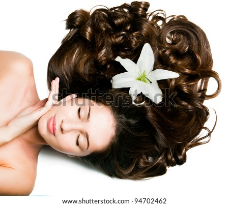 Beautiful young girl with voluminous hair and lily flower