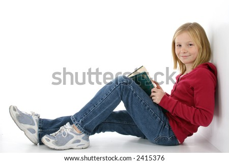 Beautiful young girl working on laptop.  Leaning against wall.