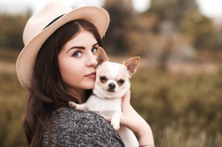 Beautiful young girl 20-24 year old holding pet dog chihuahua outdoors. Looking at camera. Togetherness.