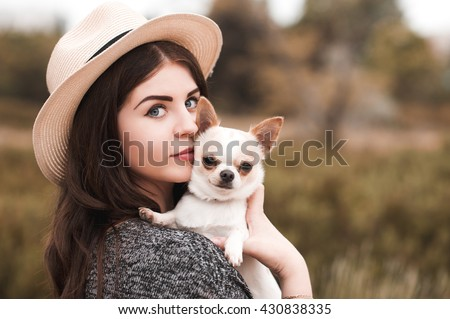 Beautiful young girl 20-24 year old holding pet dog chihuahua outdoors. Looking at camera. Togetherness. Photo stock ©