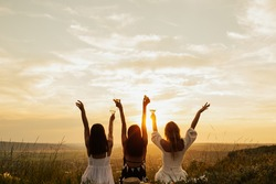 Beautiful young girls girlfriends on a picnic on a summer day. The concept of leisure, privacy, communication, vacation. Group of women enjoying picnic in the countryside with the perfect sunset.