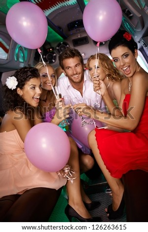 Beautiful young girls having party fun in limousine with handsome man.