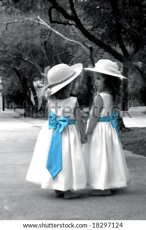 Beautiful young girls in white dresses with blue bows walk holding hands in a garden.  They are wearing hats and photo is black and white.