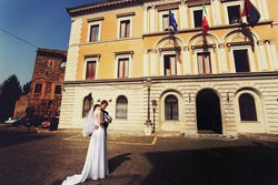 beautiful young gorgeous stylish brunette bride and groom on the background tivoli city hall italy