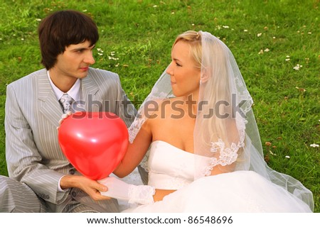 Beautiful young groom and bride wearing white dress sitting on green grass, keep red balloon heart and look at each other
