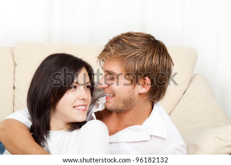 beautiful young happy couple  laying on couch happy smile looking to each other, portrait of lovely young man and woman hug, embrace on the sofa