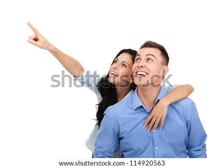 beautiful young happy couple love smiling embracing point finger to empty copy space, man and woman smile looking up, isolated over white background