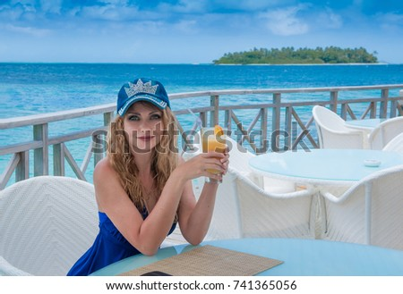 Beautiful Young Happy Girl on the Exotic Island on the Ocean Shore rejoices, the concept of tourism is a luxury vacation vacation and vacation, travel sea, drinks juice breakfast in the hotel smiles #741365056
