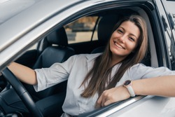Beautiful young happy smiling woman driving her car.
