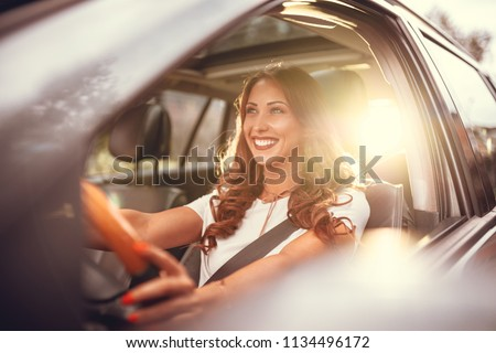 Beautiful young happy smiling woman driving her new car at sunset.