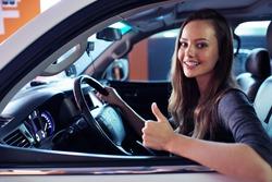Beautiful young happy woman in car. Attractive  smiling caucasian girl sitting in white auto. pretty female person driving big car suv