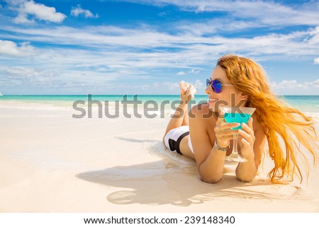 Beautiful young happy woman laying on the beach enjoying sunny weather looking on the ocean view. Tropical nature paradise getaway travel vacation tourism concept. Positive emotion face expression