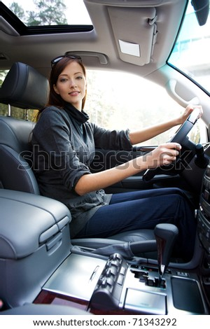 beautiful young happy woman posing inside of  the new car