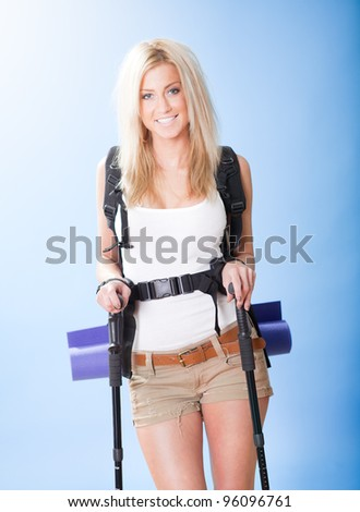 Beautiful young hiking woman  with backpack and jogging sticks