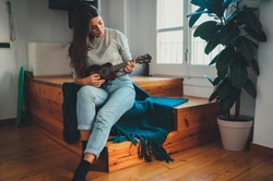 Beautiful Young Hipster Girl in casual clothes Learning to play ukulele guitar sitting on wooden stairs at home, Young Beginner Woman playing ukulele, Hobby leisure Time Learning Concept