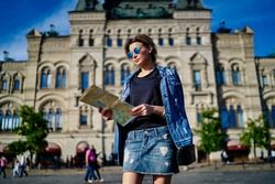 Beautiful young hipster girl in jeans wear looking at map searching direction route in touristic city, trendy dressed female traveller in sunglasses choosing route during getaway trip for recreating