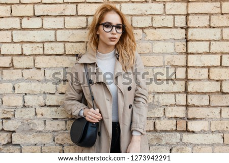 Beautiful young hipster woman in trendy glasses in a trendy lightweight coat in a white T-shirt with a black leather handbag stands near a white brick wall. Charming stylish girl. #1273942291