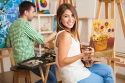 Beautiful young Hispanic woman and a handsome man attending a painting workshop together and having fun