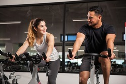 Beautiful young Hispanic woman flirting and talking to a guy while they both do some spinning at a gym. Focus on woman