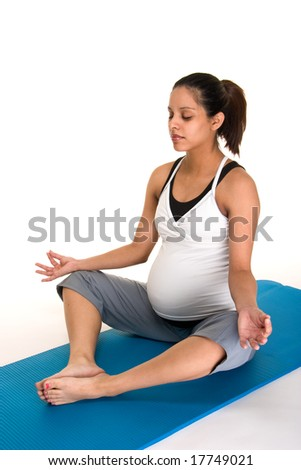 Beautiful young, Hispanic woman meditating in a yoga fitness workout to keep herself physically fit during her pregnancy.  Shot on white background.