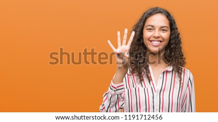 Beautiful young hispanic woman showing and pointing up with fingers number four while smiling confident and happy. #1191712456