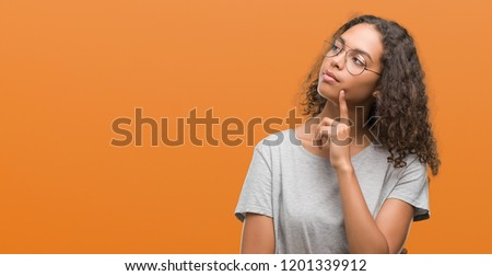 Beautiful young hispanic woman wearing glasses with hand on chin thinking about question, pensive expression. Smiling with thoughtful face. Doubt concept.