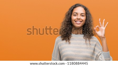 Beautiful young hispanic woman wearing stripes sweater smiling positive doing ok sign with hand and fingers. Successful expression. #1180884445