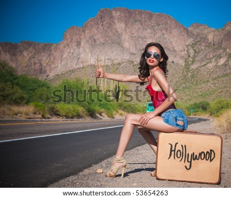 Beautiful young Hollywood hopeful hitching a lift on a desert road in California on a hot day.