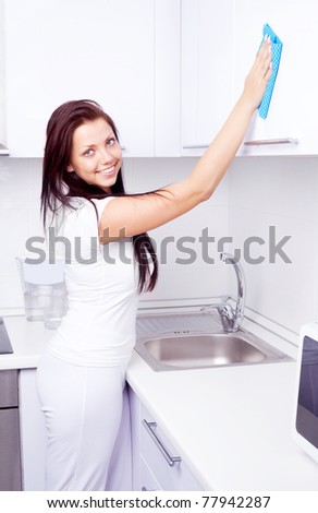 beautiful young housewife cleaning the furniture in the kitchen