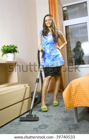 beautiful young housewife with vacuum cleaner in a room