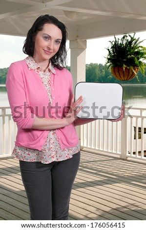 Beautiful young housewife woman holding up a blank sign