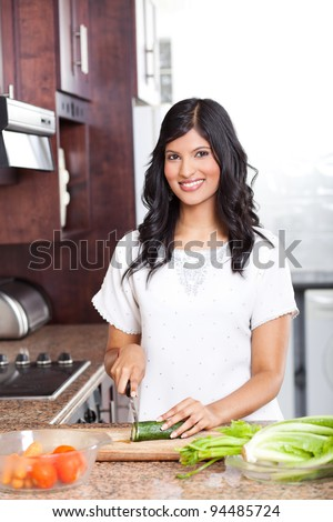 beautiful young indian woman cooking in kitchen