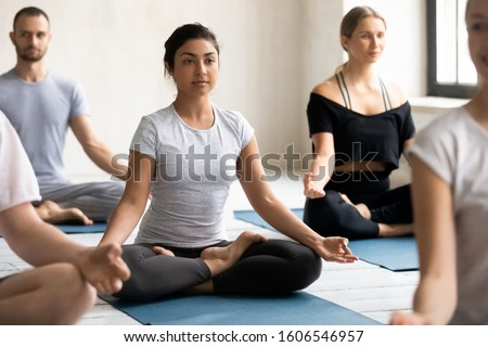 Beautiful young Indian woman doing Padmasana exercise, diverse people practicing yoga at group lesson, sitting in Lotus pose on mat, stress relief, working out in modern yoga center club stock photo