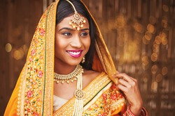 Beautiful young Indian woman dressed as a bride, wearing maang tikka and necklace with perl mala, her head covered with saree pallu