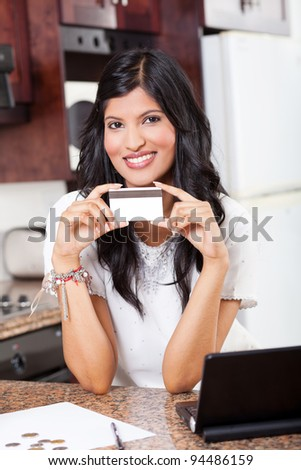 beautiful young indian woman holding credit card