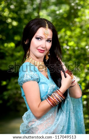 Beautiful young indian woman in traditional clothing with bridal makeup and jewelry. Bride traditionally dressed  in India. Girl bollywood dancer in Sari.