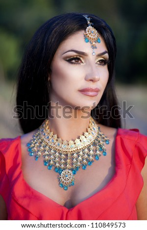 Beautiful young indian woman in traditional clothing with bridal makeup and jewelry. gorgeous brunette bride traditionally dressed Outdoors in India. Girl bollywood  dancer in Sari and henna on hands