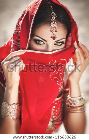 Beautiful young indian woman in traditional clothing with bridal makeup and jewelry. gorgeous brunette bride traditionally dressed Outdoors in India. Girl bollywood dancer in Sari. Arabian bellydancer