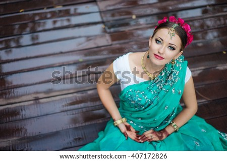 Beautiful young indian woman in traditional clothing with bridal makeup and jewelry. gorgeous  bride traditionally dressed Outdoors in India. Girl bollywood dancer in Sari and henna on hands